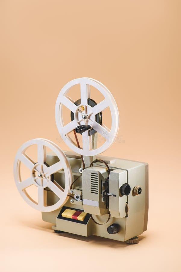 关闭老电影放映机看法在米黄背景的 免版税库存图片