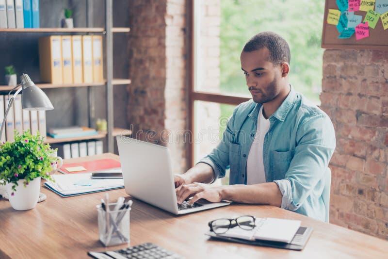 关闭考虑年轻非洲英俊的人 他佩带偶然聪明,坐在工作场所,看在膝上型计算机屏幕, 免版税库存图片