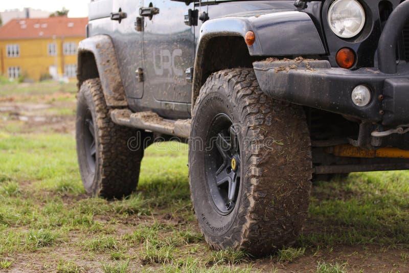 关闭肮脏的吉普争吵者在驾驶重越野以后在湿地形 在泥和土弄脏的轮子 站立在绿色gras 免版税库存图片