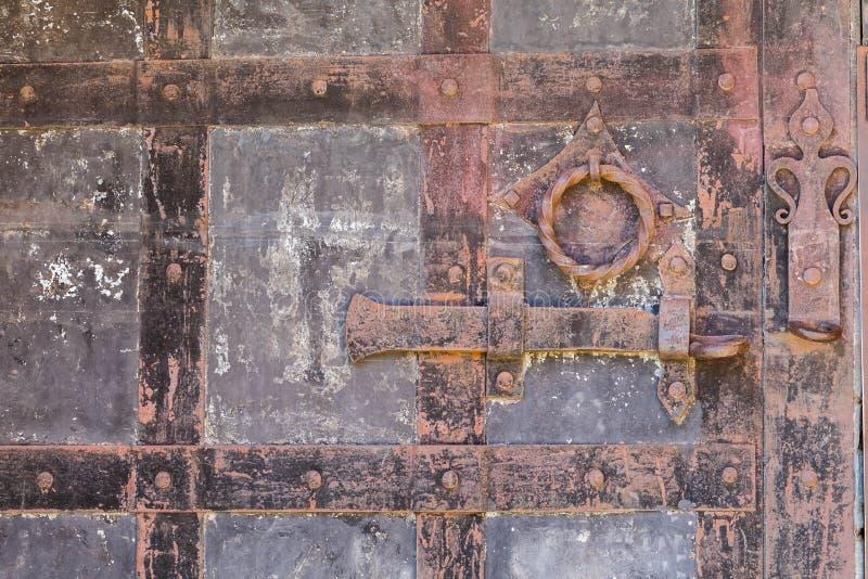 关闭背景在一个老铁门的一个难看的东西生锈的金属螺栓 免版税库存照片