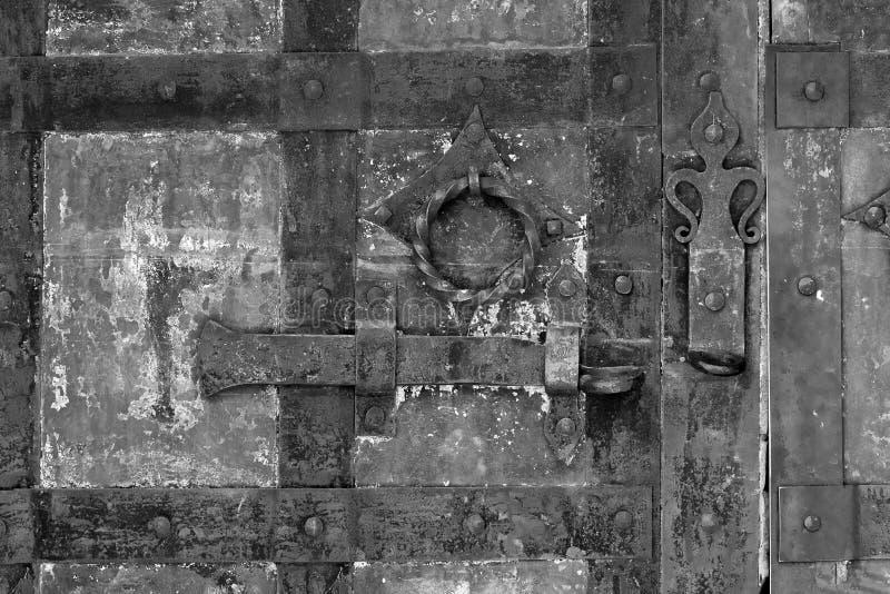 关闭背景在一个老铁门的一个黑难看的东西金属螺栓 库存图片