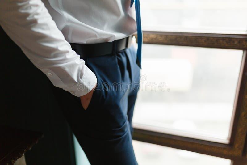 关闭腕子的时尚图象在许多的裤子的 详述商人的身体 在一件白色衬衣的人的手,黑暗蓝色 免版税库存图片