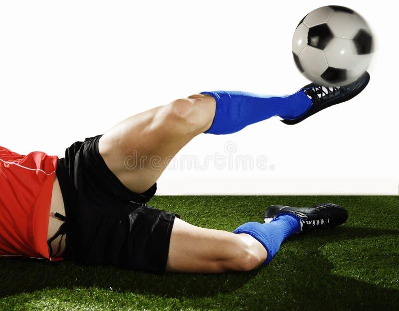 关闭腿和足球运动员足球鞋子做滑车和踢球的行动的 免版税图库摄影