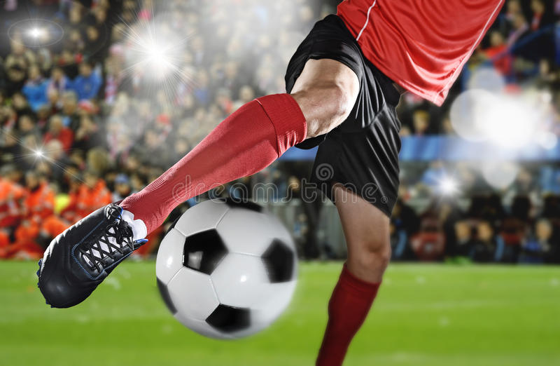 关闭腿和足球运动员足球鞋子踢球的行动的使用在体育场内 库存图片