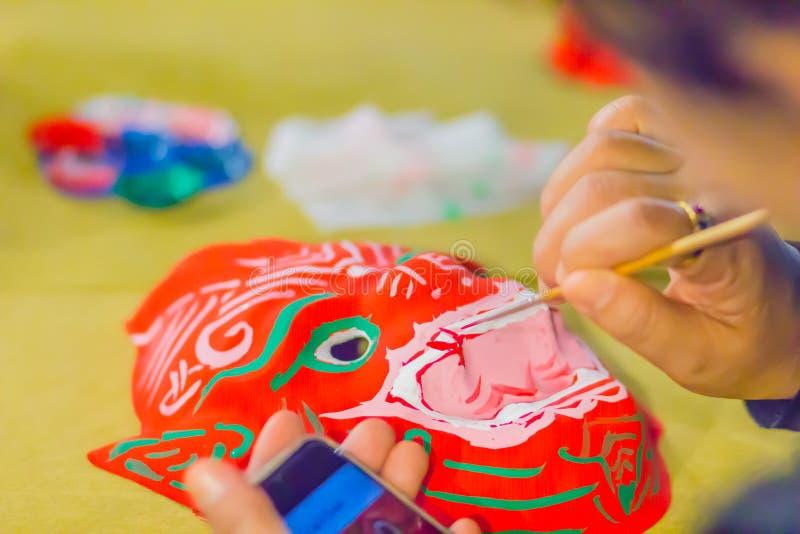 关闭艺术家的手,当绘在Khon面具由用途刷子和草稿的红颜色从巧妙的电话时 图库摄影