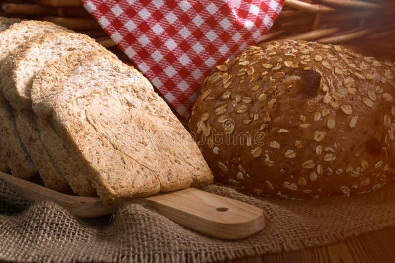 关闭芝麻小圆面包和切的面包在木板材 免版税库存图片
