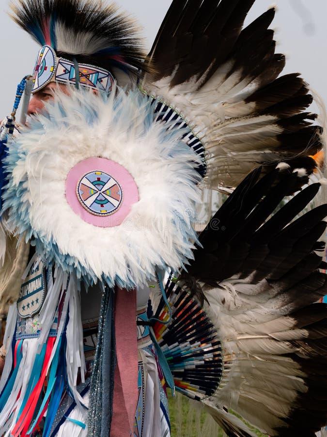 关闭花梢舞蹈家在有羽毛头饰和熙来攘往的战俘Wow 库存照片