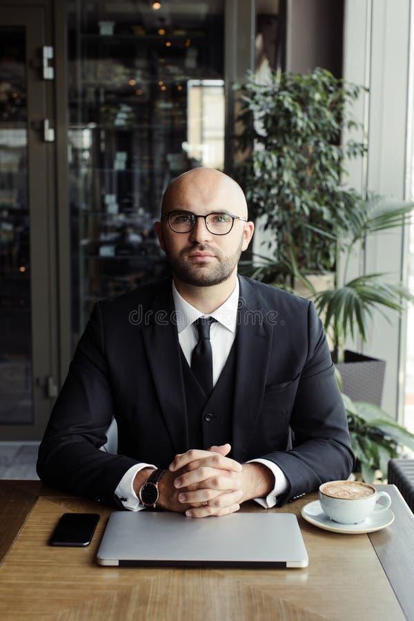 关闭英俊的商人,研究膝上型计算机在餐馆 免版税库存图片