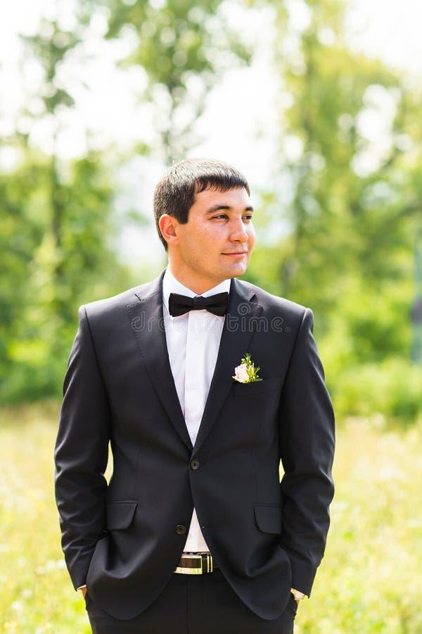 关闭英俊的时髦的新郎画象黑经典衣服的户外 库存照片