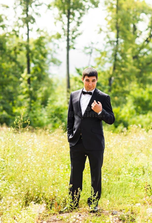 关闭英俊的时髦的新郎画象黑经典衣服的户外 库存图片