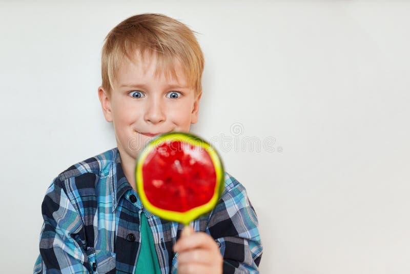 关闭英俊的男孩画象有在控制中衬衣穿戴的金发和蓝眼睛的拿着巨大的甜糖果在他的ha 免版税库存照片