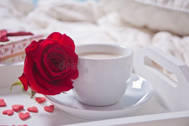 关闭茶与红色玫瑰的和在桌上的小糖果心脏 图库摄影