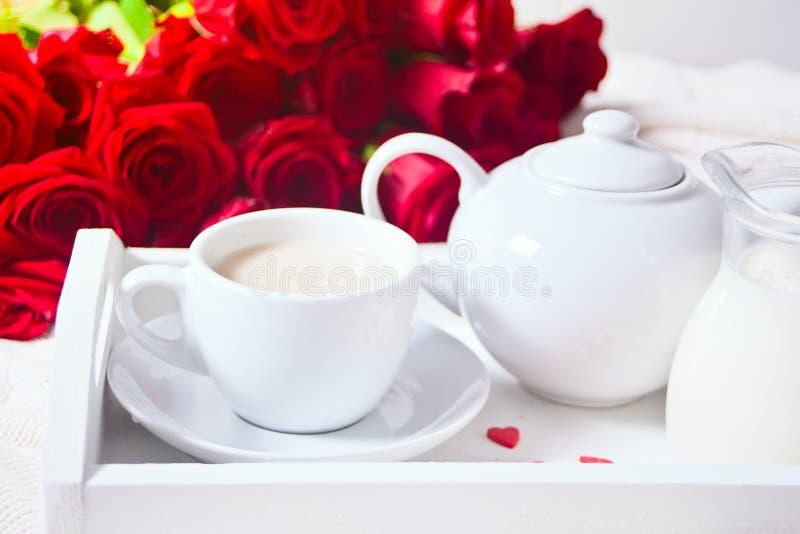 关闭茶与红色玫瑰的在白色盘子 免版税库存图片