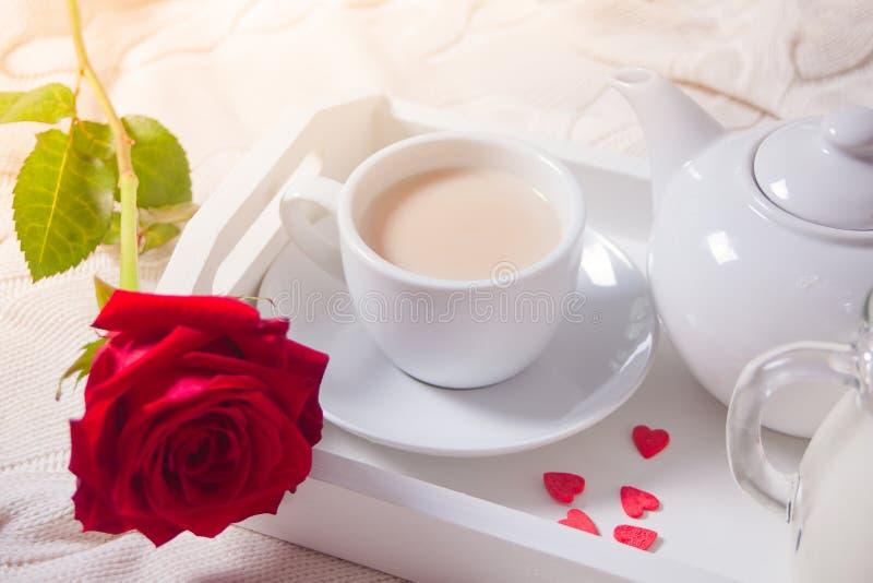 关闭茶与红色玫瑰的在白色盘子 免版税库存照片
