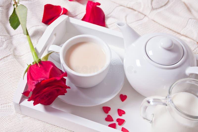 关闭茶与红色玫瑰的在白色盘子 库存图片