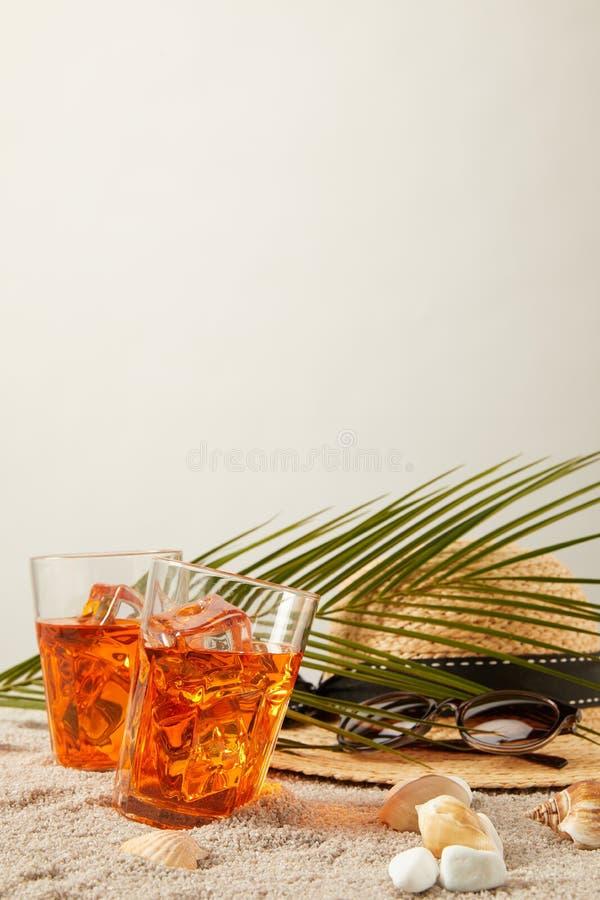 关闭草帽、鸡尾酒、贝壳、太阳镜和棕榈叶看法在沙子在灰色背景 图库摄影
