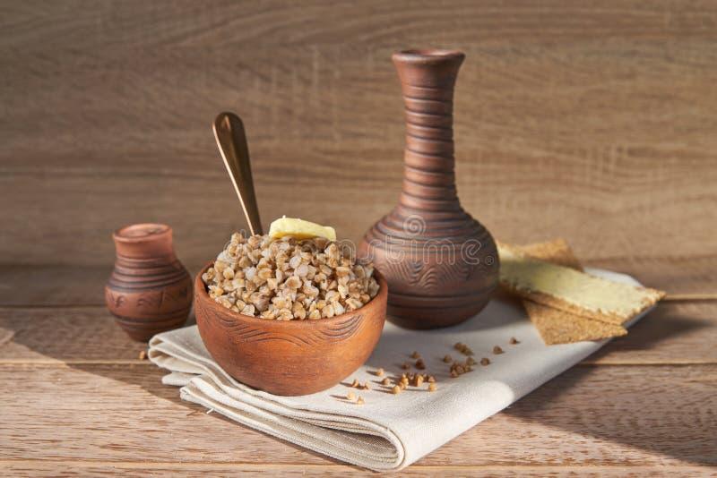 关闭荞麦粥用在一个碗的黄油在白色木背景 库存照片