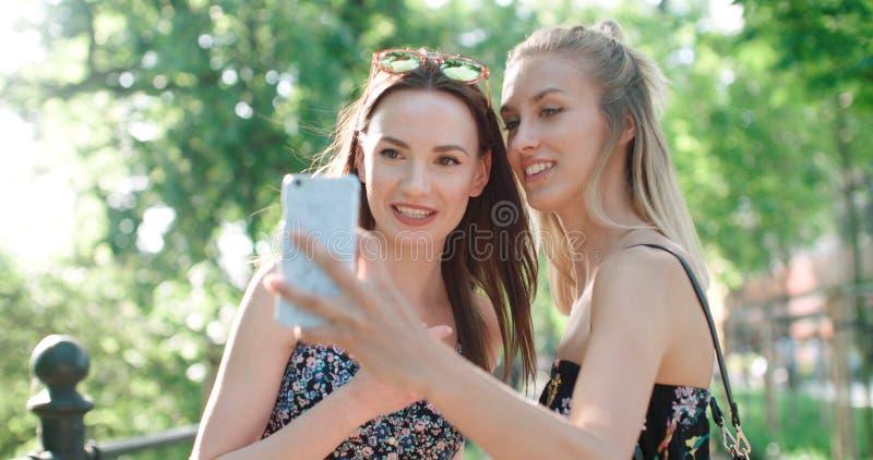 关闭获得乐趣和做selfie的两个年轻快乐的女孩画象,户外 库存照片