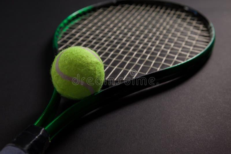 关闭萤光黄色网球拍和球 库存照片
