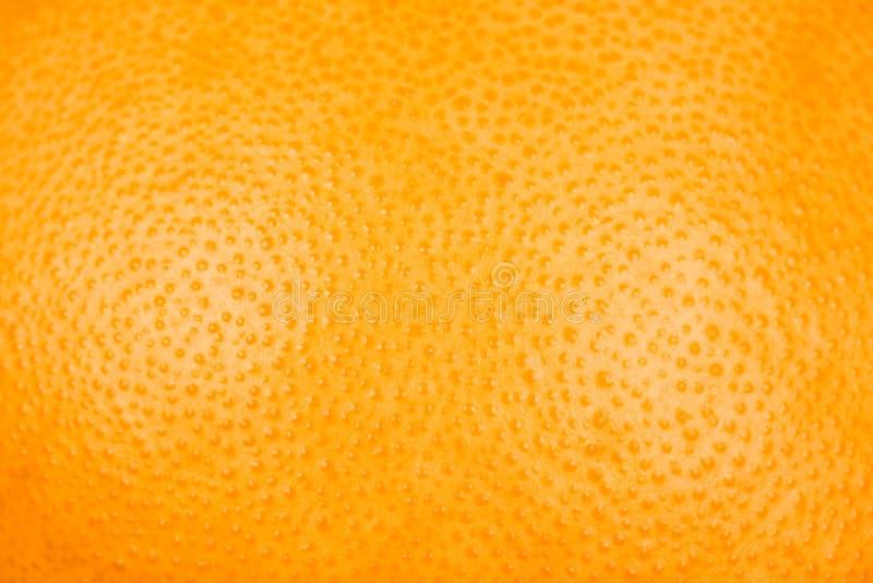 关闭葡萄柚或橙色纹理果皮或者热心 免版税库存照片