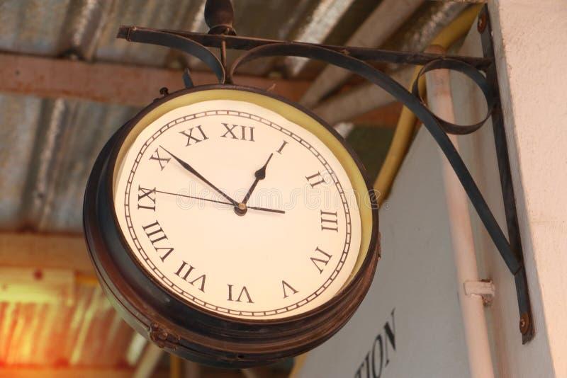 关闭葡萄酒死亡在葡萄酒锌屋顶的时钟吊在葡萄酒在亚洲的省的火车站 免版税图库摄影