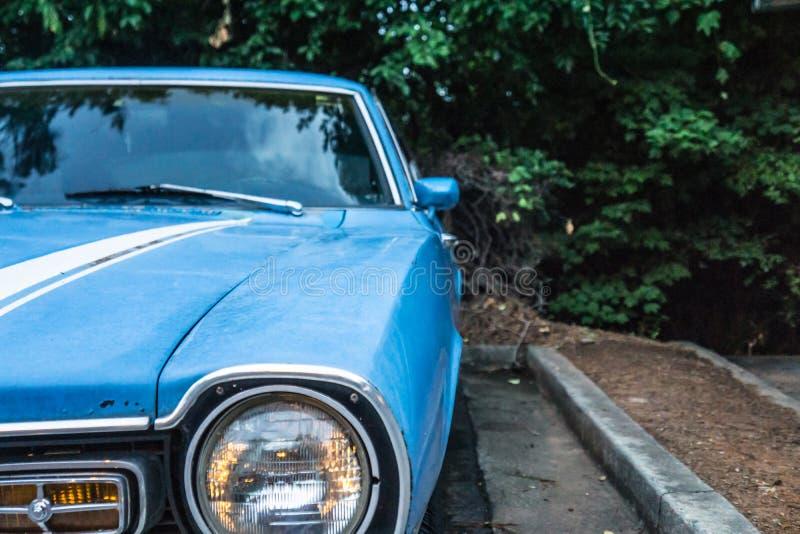 关闭葡萄酒蓝色汽车的老前灯 停放和围拢由树 免版税库存图片