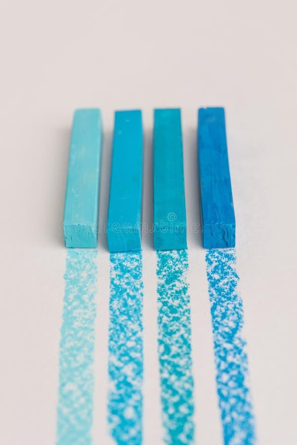 关闭蓝色在它自己的踪影l的颜色淡色蜡笔白垩 免版税库存图片