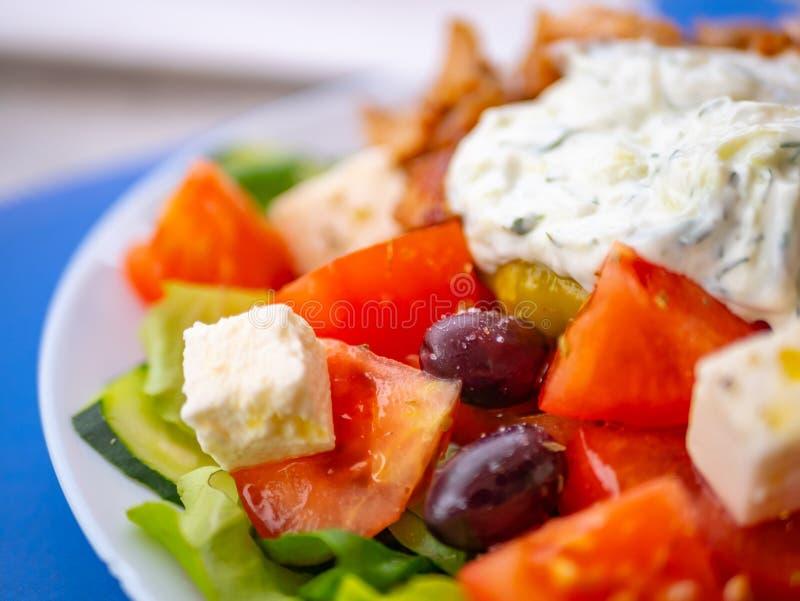 关闭蕃茄、橄榄、希腊白软干酪和切片从著名希腊沙拉的黄瓜,反对被弄脏的背景 免版税库存照片