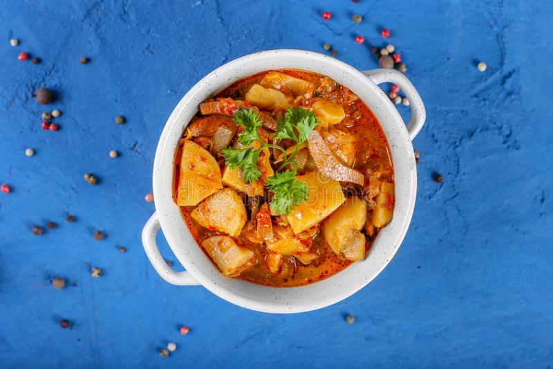 关闭藜科冈羊栖菜属植物用肉、土豆、西红柿酱和蘑菇在一个碗在石蓝色背景 r 库存照片