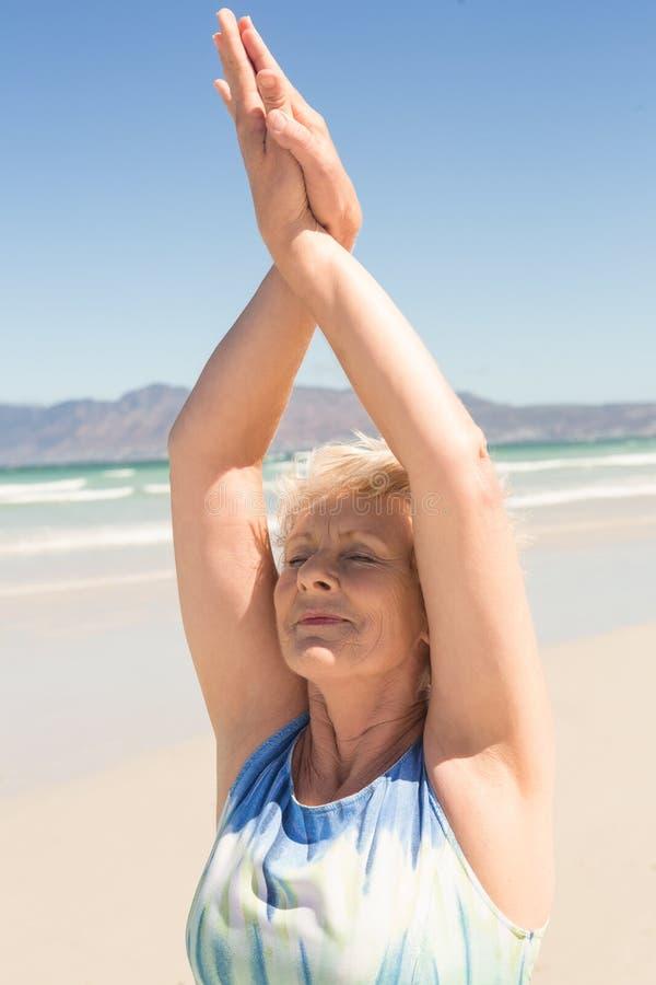 关闭行使资深的妇女,当站立在海滩时 免版税库存照片