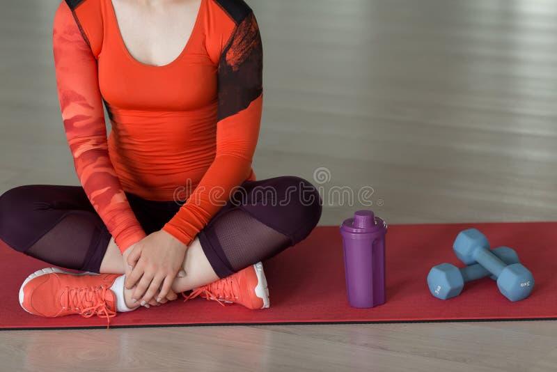 关闭衣服的年轻运动员坐地毯在哑铃旁边并且从瓶浇灌 图库摄影