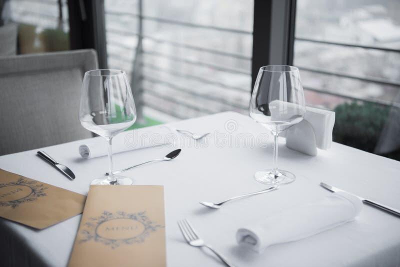 关闭被安排的利器、空的葡萄酒杯和菜单看法在桌上与白色桌布 库存照片