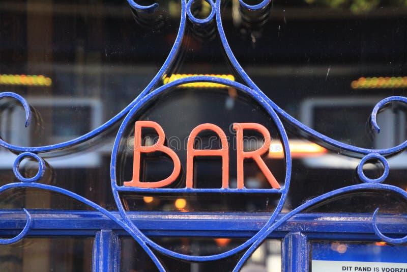 关闭被隔绝的葡萄酒减速火箭的红色和蓝色金属酒吧标志在玻璃窗 免版税库存照片