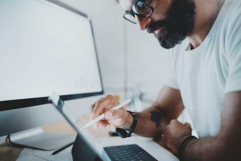 关闭观点的白色T恤杉的有胡子的人与便携式的片剂计算机一起使用 画数字式计划的设计师在 库存图片