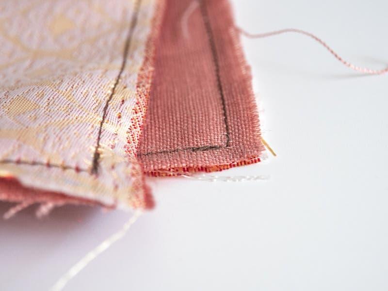 关闭解开与棕色螺纹针的桃红色橙色亚麻制织品纹理与拷贝空间 材料、纺织品和服装 免版税图库摄影