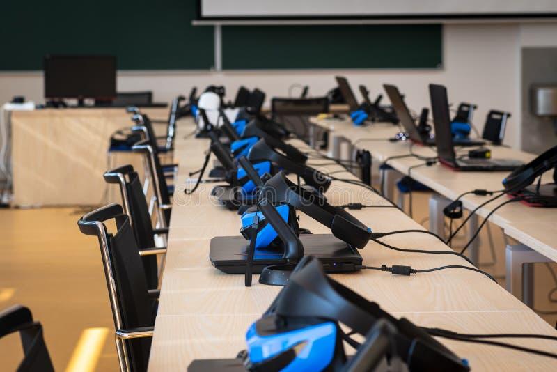 关闭许多虚拟现实VR在教室-耳机、控制器和计算机设置 库存照片