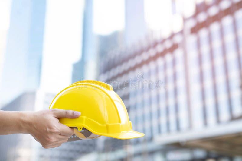 关闭设计举行男性建筑工人的手给安全工作操作的安全的黄色盔甲 免版税库存照片