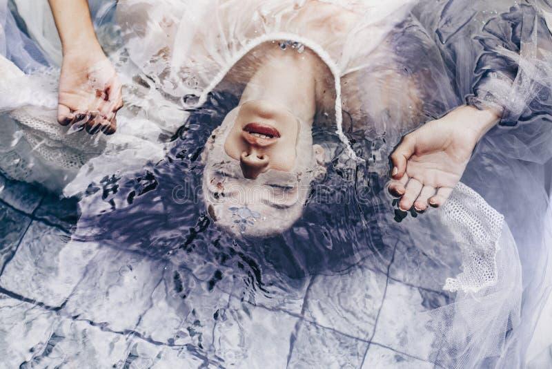 关闭说谎在与织品的水的美丽的妇女画象 图库摄影