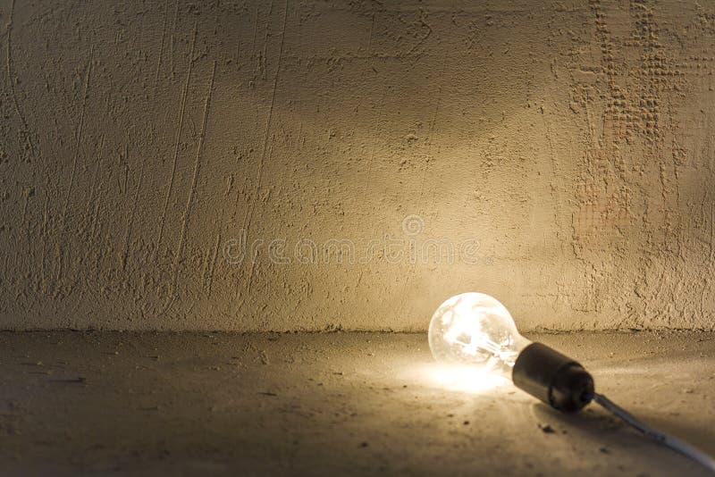 关闭说谎在地板上的电电灯泡照片发光在显示瑕疵的新鲜的涂灰泥的灰色粗砺的墙壁 电和rep 免版税库存图片