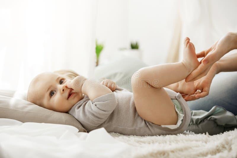 关闭说谎在床上的逗人喜爱的新出生的婴孩,看在旁边,当演奏和接触他小的腿时的母亲 婴孩 库存照片