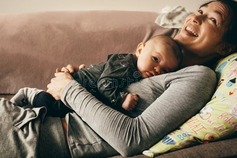 关闭说谎在有她的婴孩的长沙发的母亲 免版税库存照片