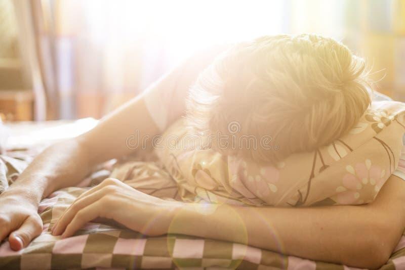 关闭说谎在mroning反对阳光throung窗口f的床睡眠的年轻男性 免版税库存照片