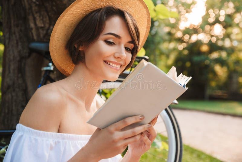 关闭读书的微笑的女孩 免版税库存图片