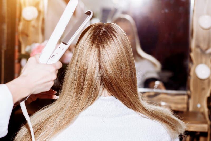 关闭调直有头发铁的过程长的金发 秀丽,发型,热称呼,角质素调直的概念 免版税库存照片