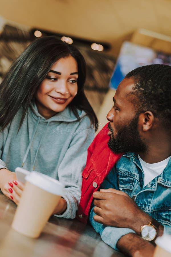 关闭谈话年轻的夫妇,当喝咖啡时 免版税库存照片