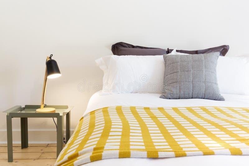 关闭豪华床和床头柜与灯 免版税图库摄影