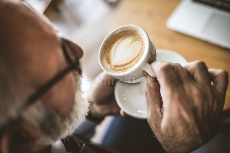关闭资深商人饮用的咖啡的图象 免版税库存图片