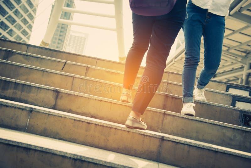 关闭走在提高的两旅行的人的腿台阶在现代城市 运动鞋和牛仔裤元素 事务和 库存图片