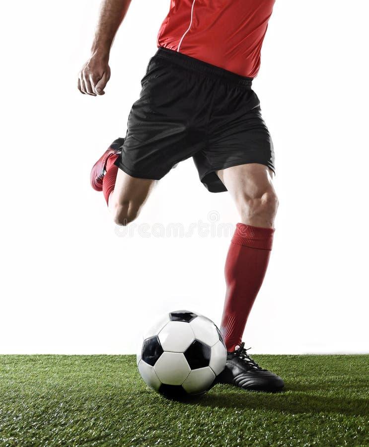 关闭足球运动员的腿红色控和踢球的袜子和黑鞋子的 免版税图库摄影