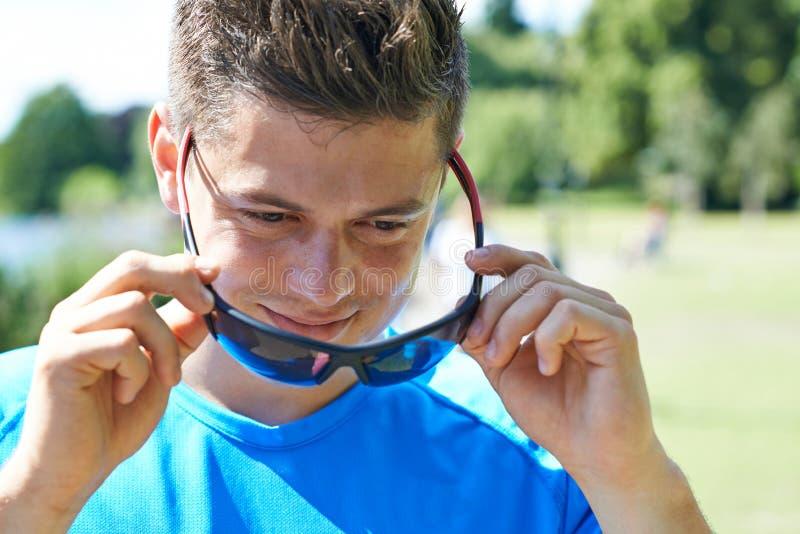 关闭跑在公园的年轻人投入在太阳镜 库存照片